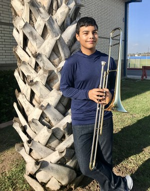 Picture of Damian Gonzalez holding his trombone, leaning against a palm tree