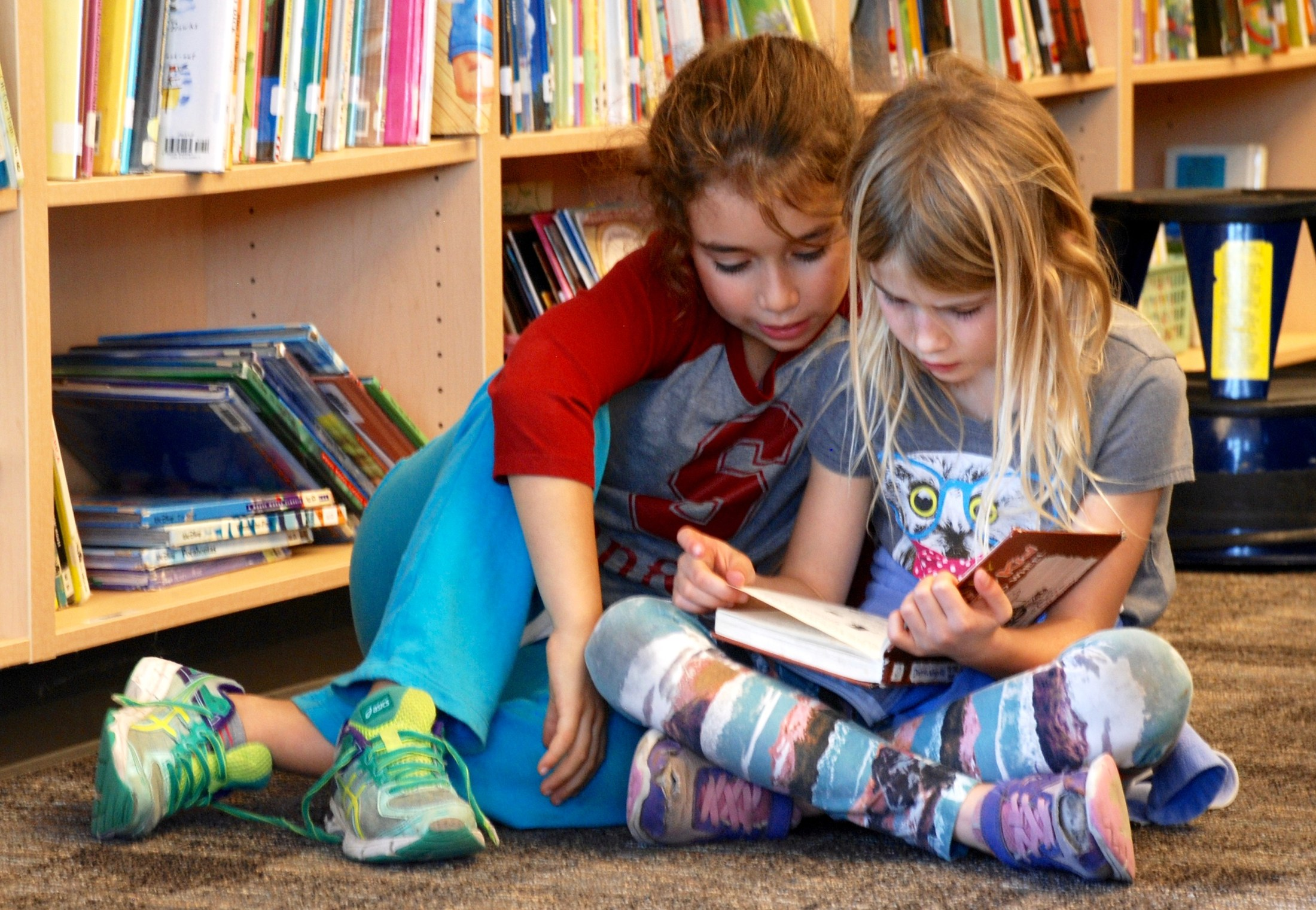 students reading in library shelves