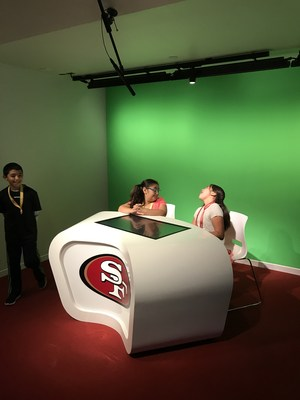 Two students practice being spots casters at a news desk