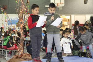 Students on a stage reading at Camas Grandparent's Day