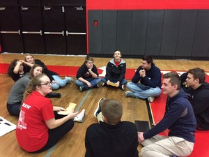 Freshmen students sit in a small group circle in the gymnasium.