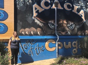 Sara Eastman in front of an Acacia sign.