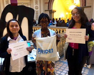 Three girls pose with certificates of achievement.