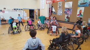Students play wheelchair basketball.