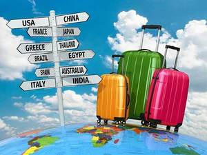 A directional sign pointing to several different countries, with a variety of luggage.