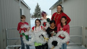 Teacher and students with handmade Christmas wreaths.