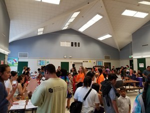 Families gather in the cafeteria to speak to local community groups
