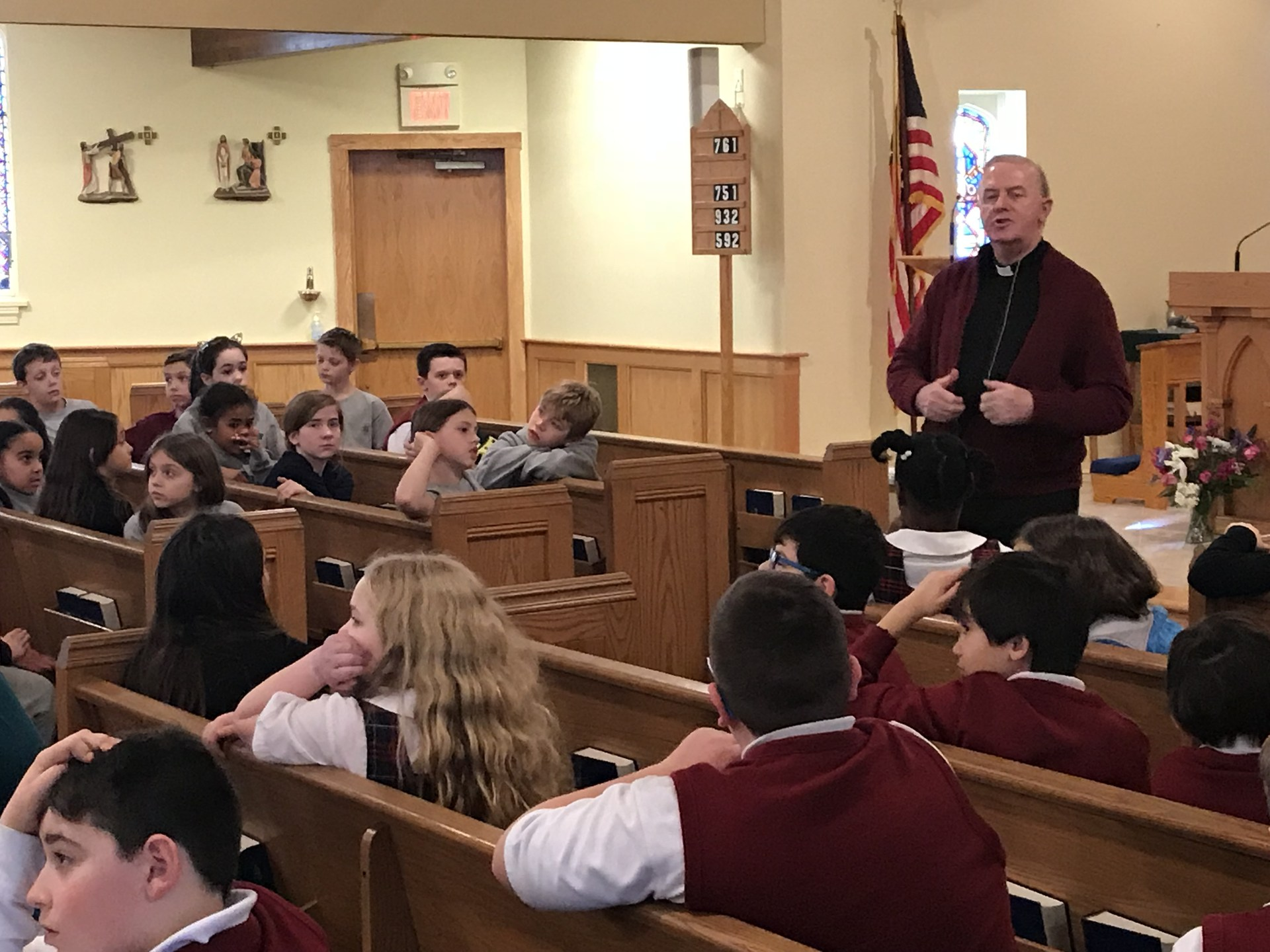 Priest taking question from fourth-grade student during retreat