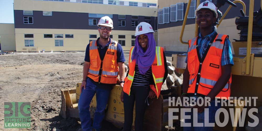 Three young, smiling workers with hard hats and safety vests