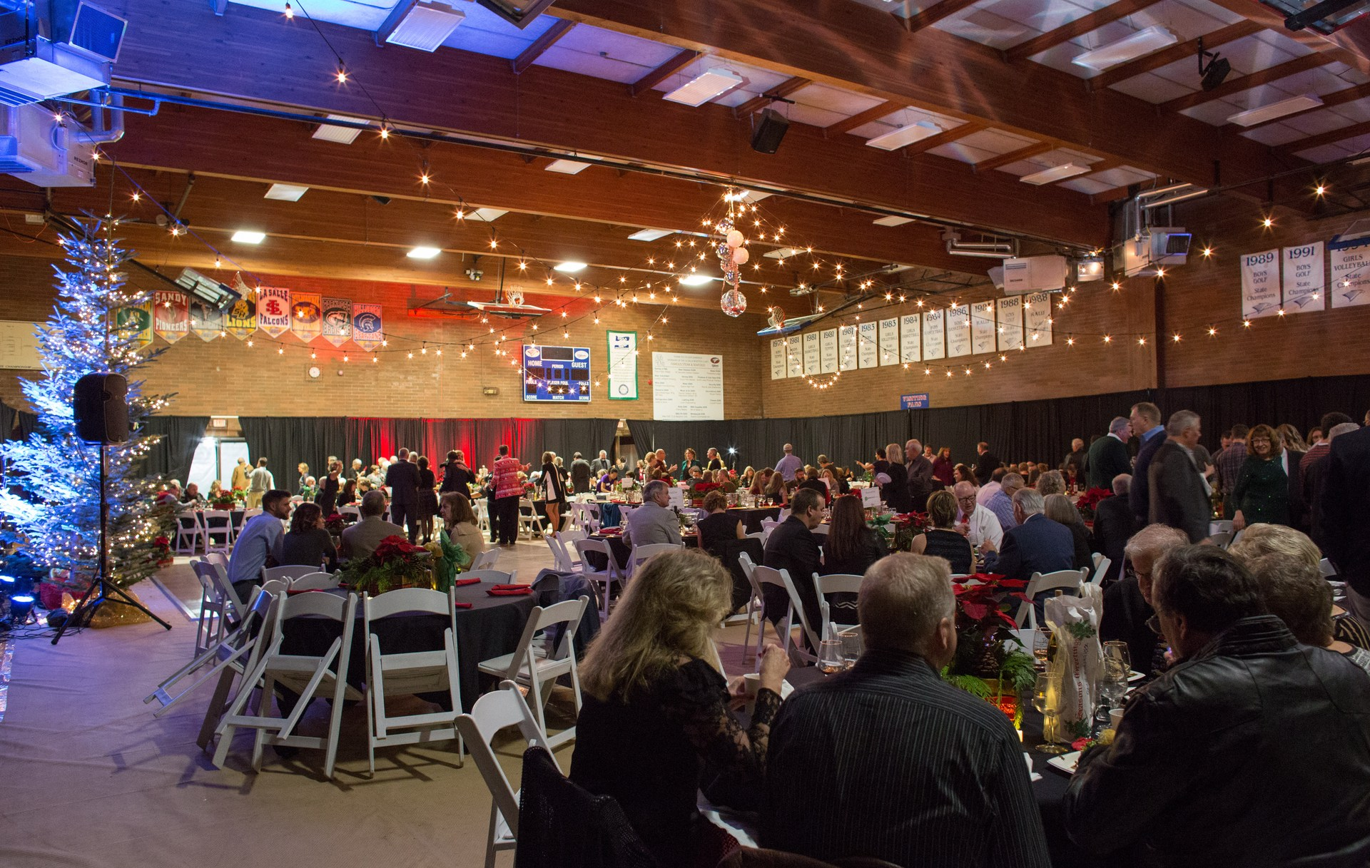 Banquet hall full of people sitting at tables.