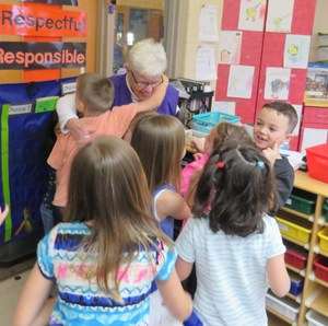 Longtime volunteer Ann Humphrey gets hugs from kindergarten students.