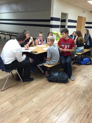 Principal Slamer and students sitting at a table.