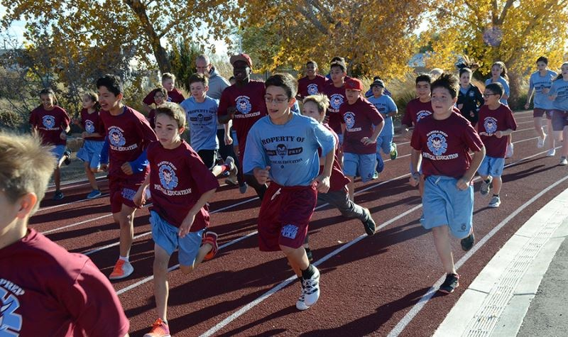 Sixth grade students run on the track during PE