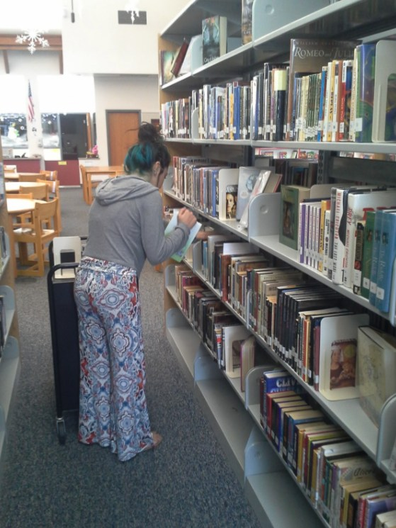 Student cataloging books in library.
