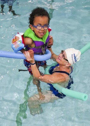 Young camper in the pool with teacher assistant