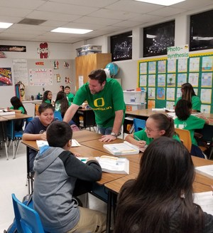 BPUSD_HONOR_1: Kenmore Elementary School Bernardo Perdices, clad in University of Oregon green, works with students on a math performance task.