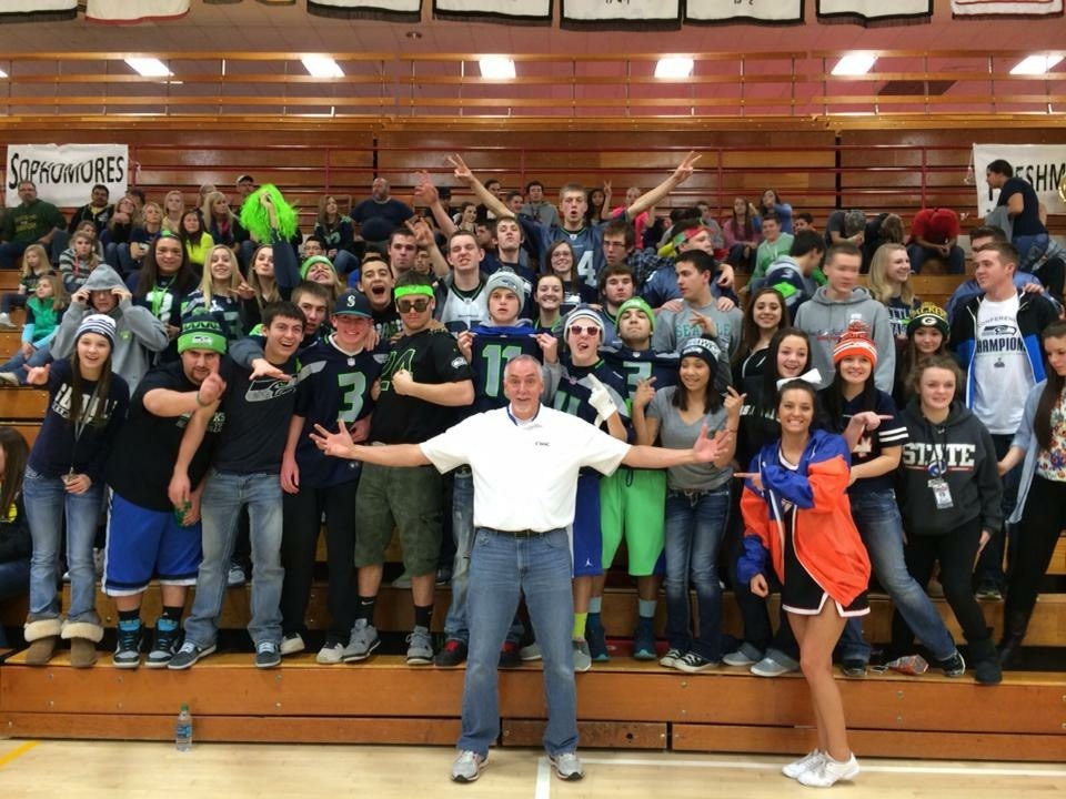 Mr. Dave Cullen (2016 Winner) - Athletic Director, standing with open arms with the student body at an assembly!