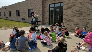 Students listen to directions of what they will do to plant their flowers.