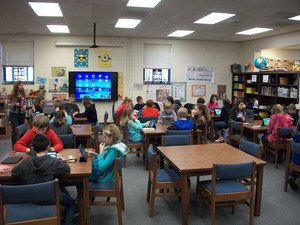 Class is working with iPads in media center.