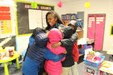 Students with coats hugging teacher