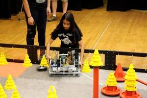 Robotics Team Member Giselle Alaniz positions the robot for a test run.