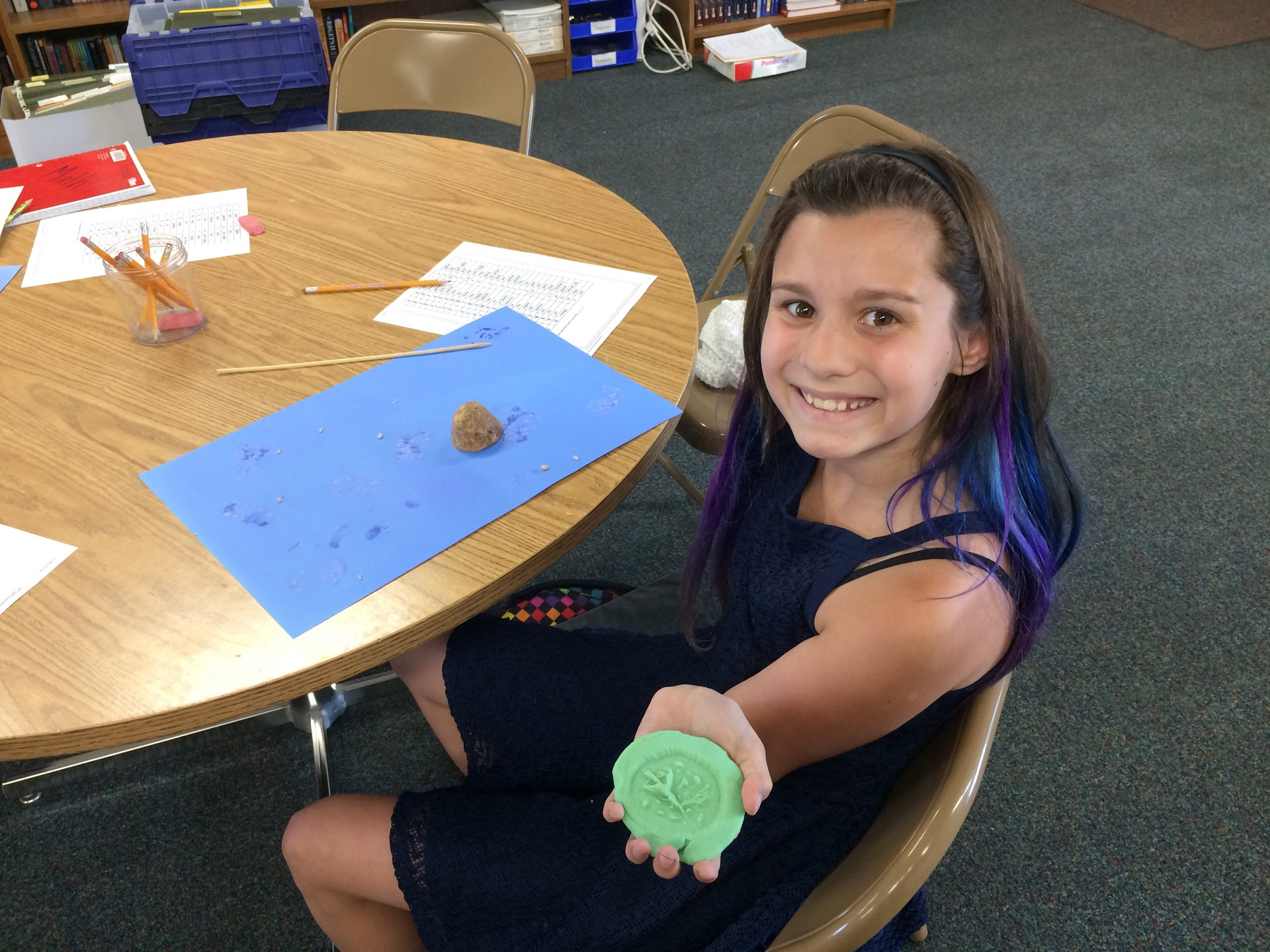 Student showing her Greek coin.