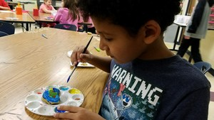 A student paints his rock.