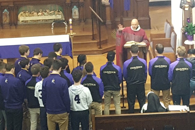 Student-athletes receive a blessing from Fr. Sam Esposito