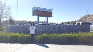Diana Riopedre in front of a Rancho Viejo Middle School sign.