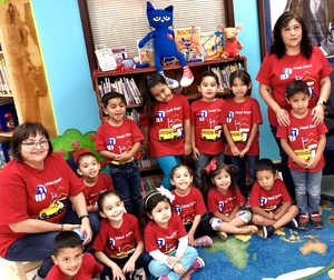 Head Start visitors pose in library.