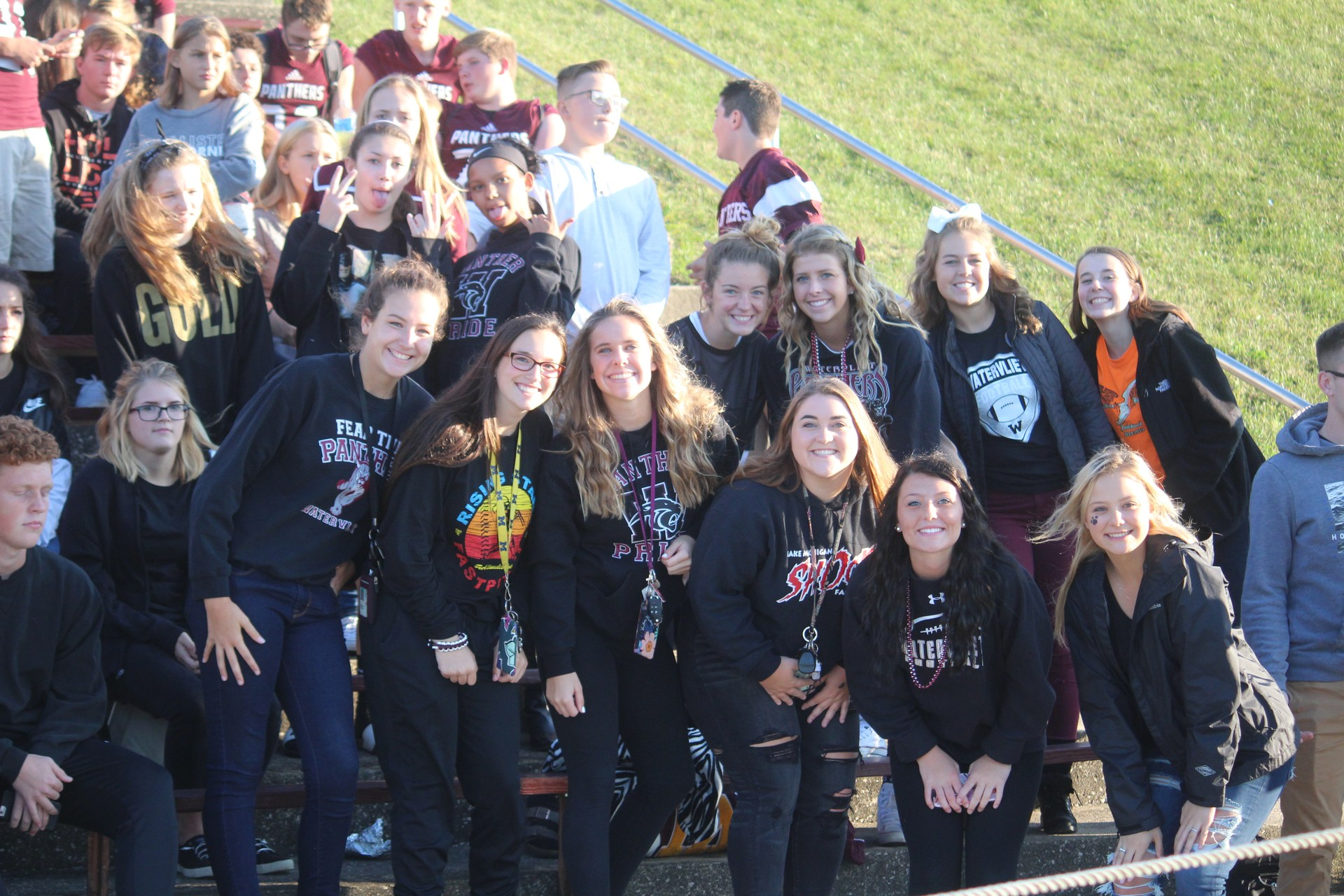 students posing at football game
