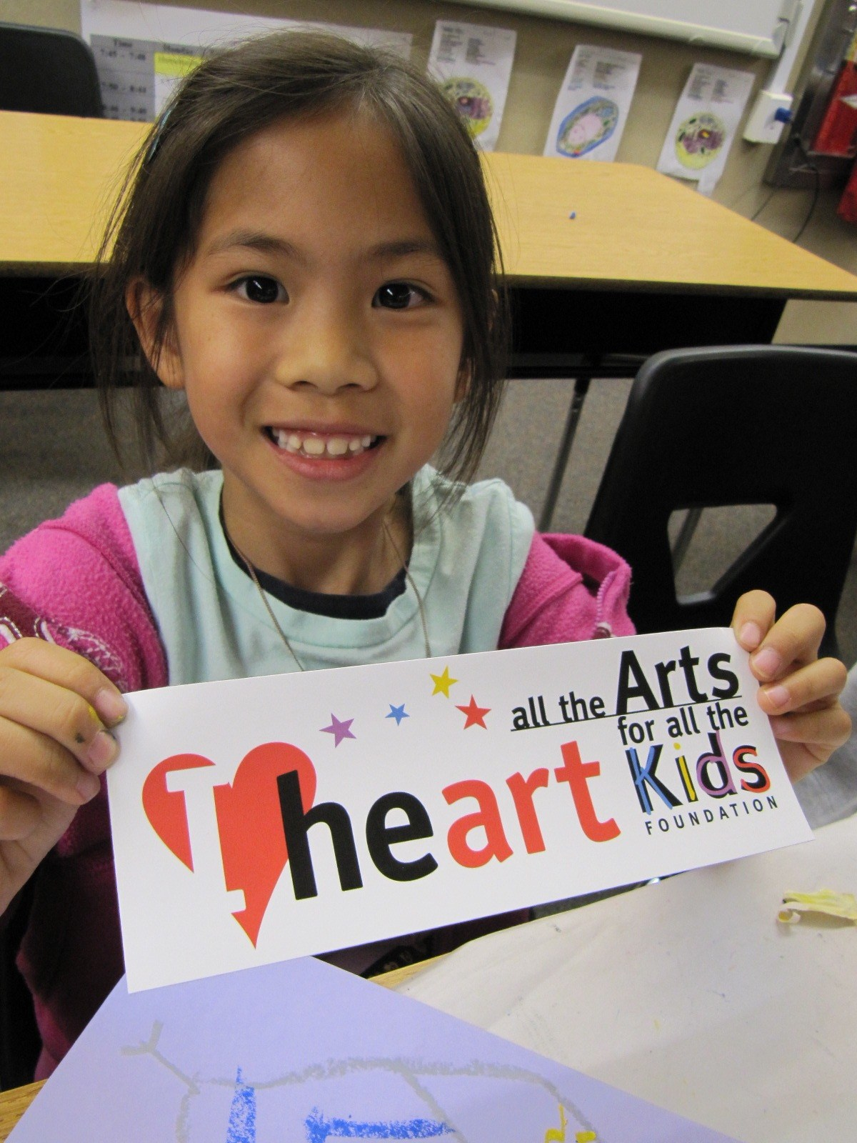 A girl showing All the Arts For All the Kids bumper sticker.