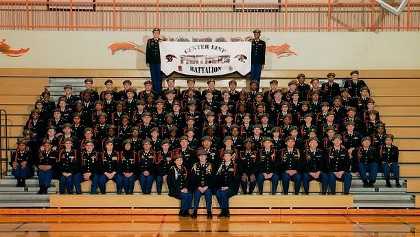 Center Line High School Panther Battalion in uniform on gym bleachers with banner