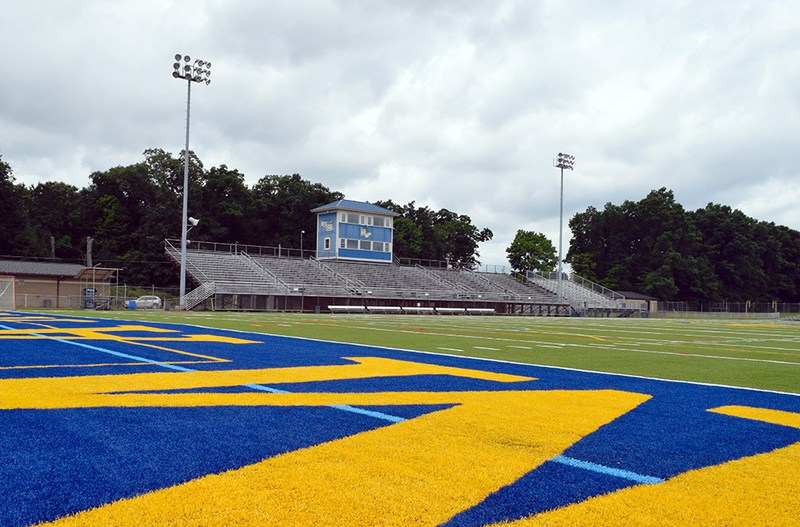 A football field with stands and a press box in the distance.