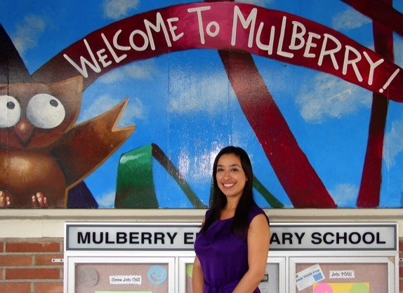Principal, Ms. Salamanca, in front of the Welcome to Mulberry sign