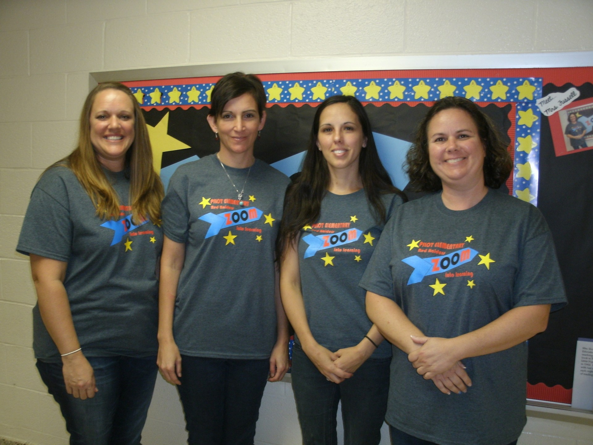 Four kindergarten teachers are standing in front of a bulletin board.