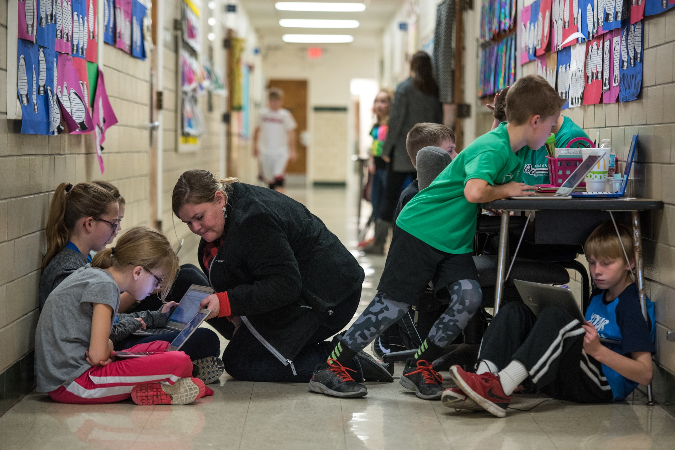 A teachers aide at Crosby Elementary School instructs students in a hallway, one of the few places she has available for teaching.