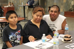 Families complete a worksheet at the Dinner & Bilingual Family Night