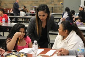 Satus Vice Principal helps a family complete a worksheet at the Dinner & Bilingual Family Night