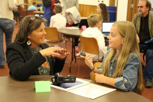 9-R TOSA Hallie Whitney speaks with student at the Great Brains Expo.