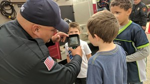 A firefighters shows students how a thermal imaging camera works.