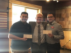 Three men huddled together two holding checks to be donated.