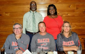 A photo of the Baker High School Softball Coaches seated at a restaurant table with the Superintendent and their Principal standing behind them