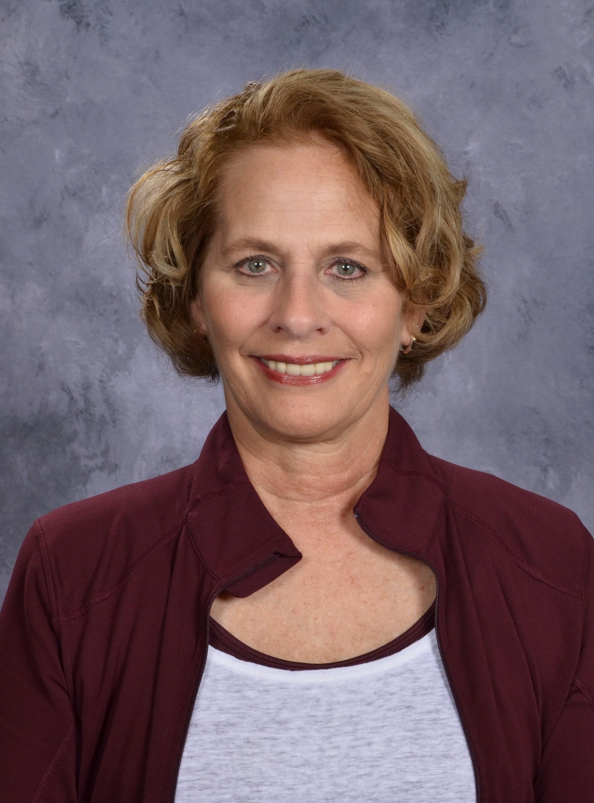 woman with short blondish hair wearing burgundy shirt