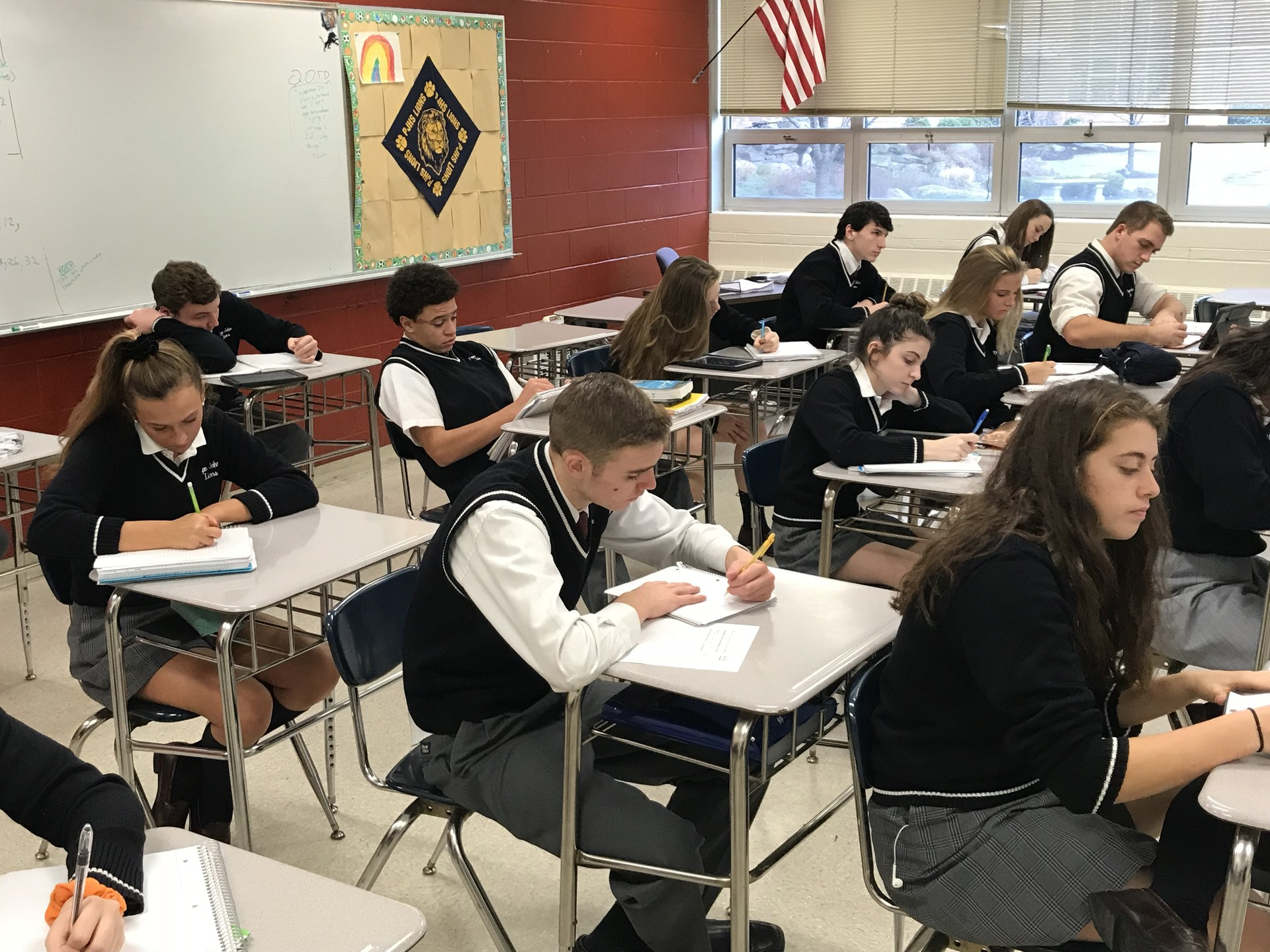 Students writing notes down in class