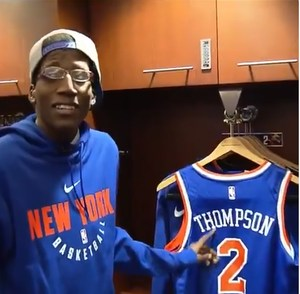 Kevin in the Knick lockeroom looking has a jersey with his name