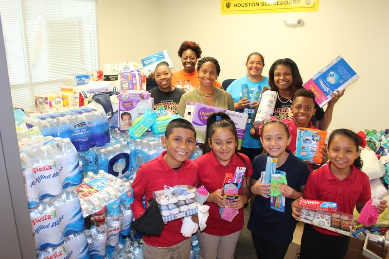 Students and staff showing the donations collected by the campus