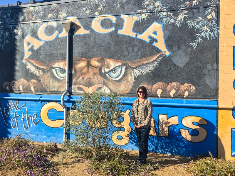 Mrs. Liz White in front of a painting of the Acacia Cougar.