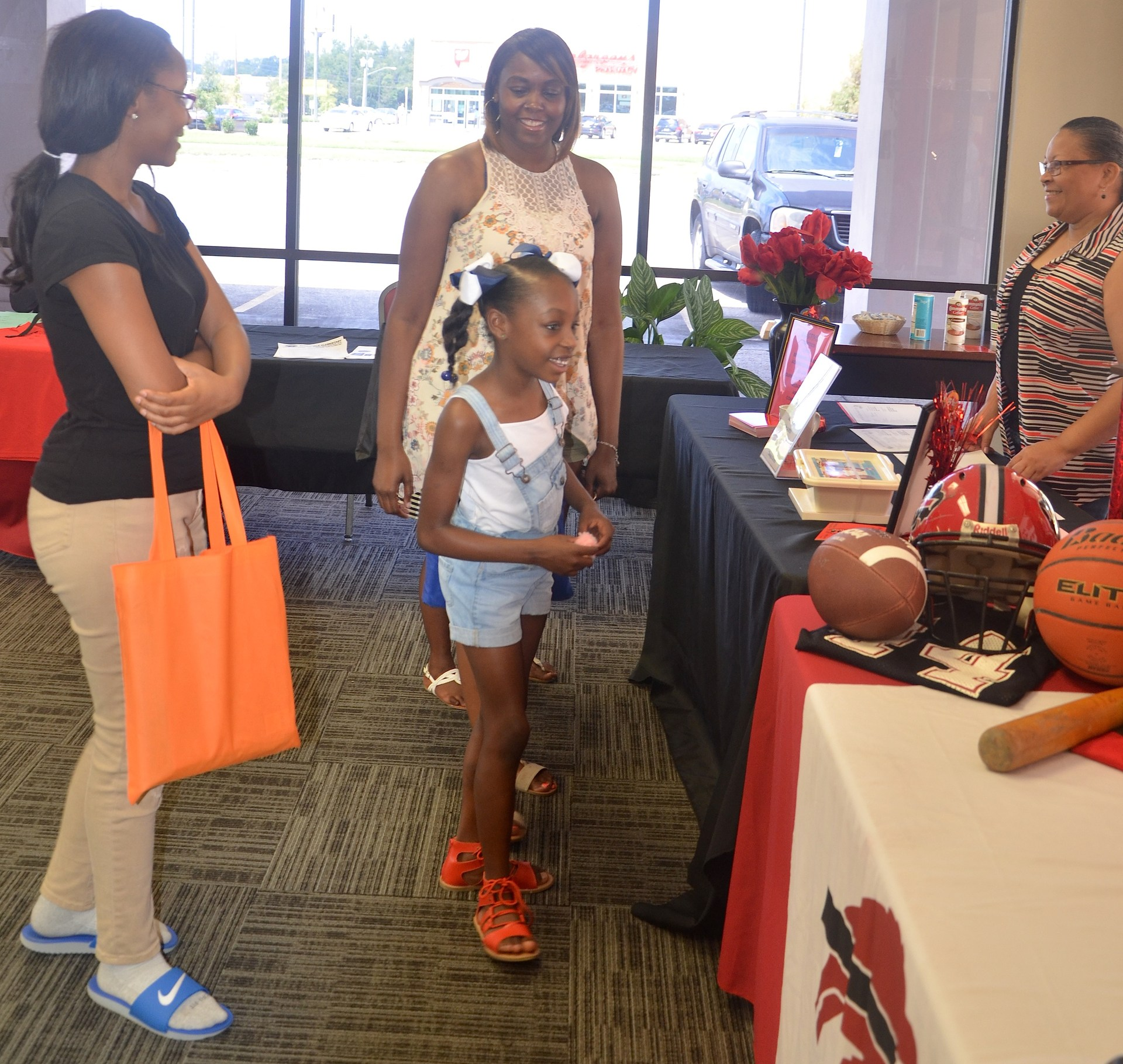 A little girl and several adult ladies checking out the Baker High Expo table