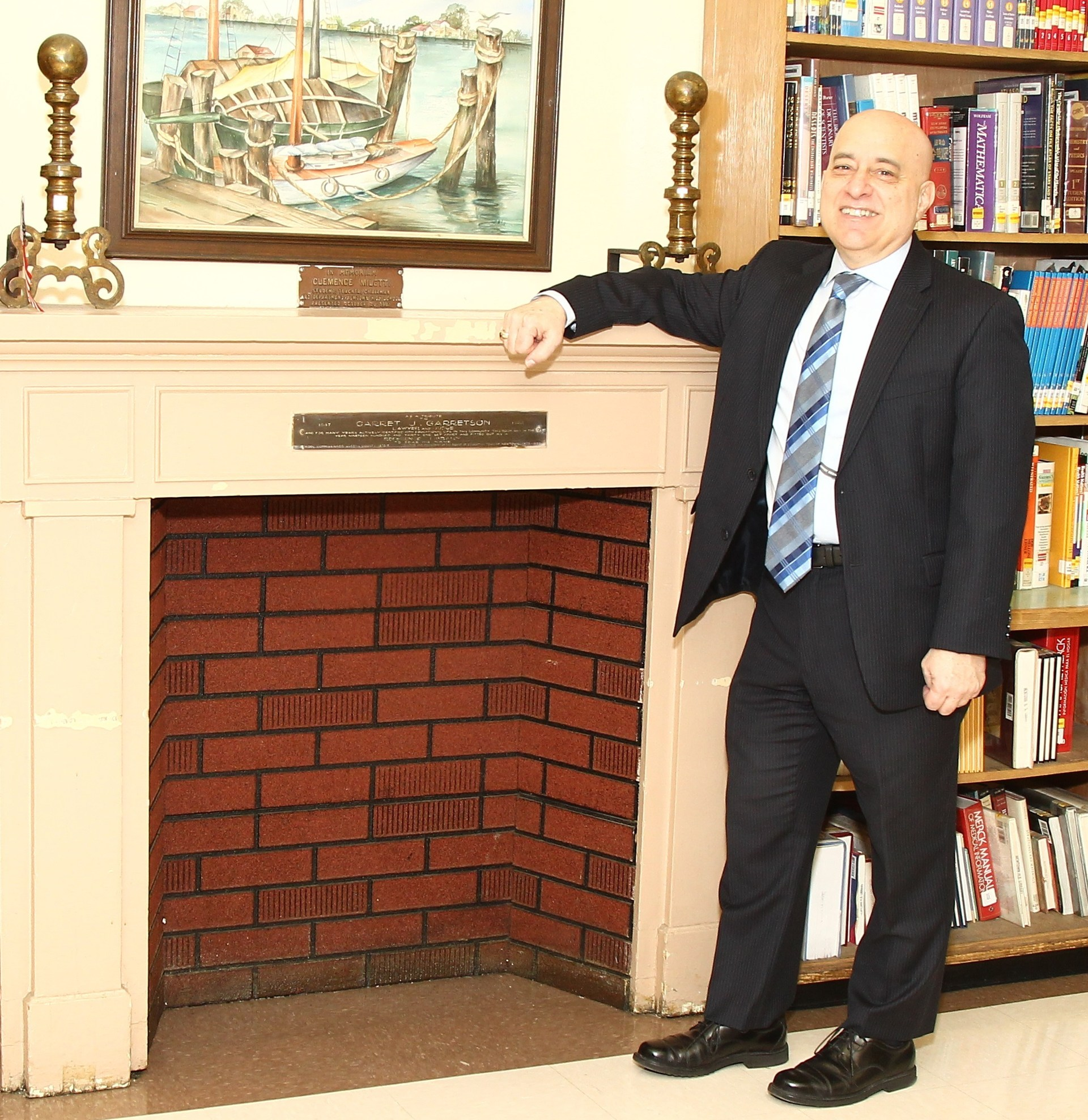 Principal standing beside fireplace.